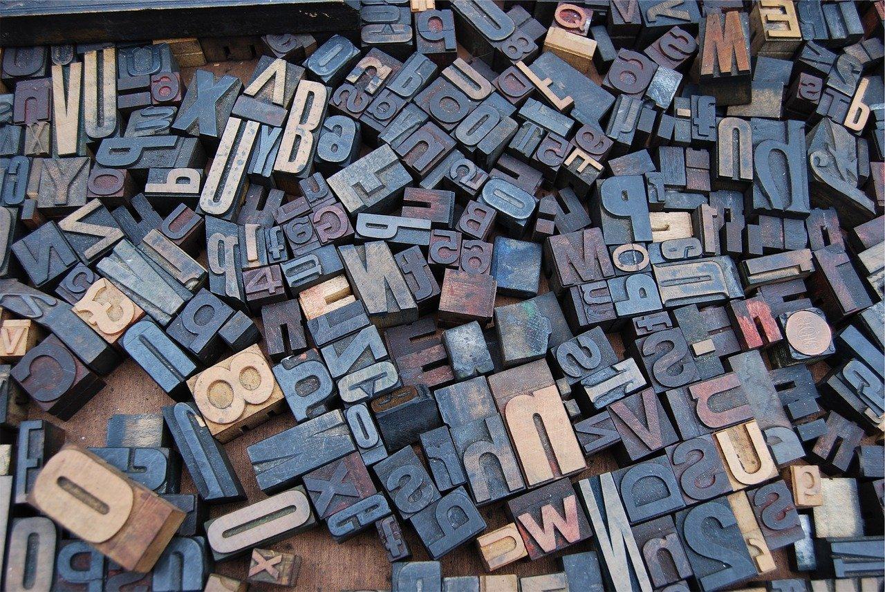 un centinaio di lettere metalliche su supporti di legno per scegliere una password sicura